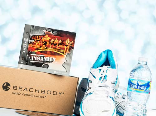 Beachbody logo'd box with DVD set, pair of running shoes and bottled water