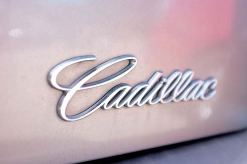Close up of the Cadilac emblem on a pink car