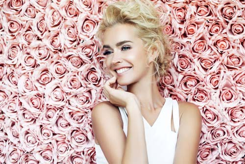 A beautiful blonde woman standing in front of a wall of pink roses