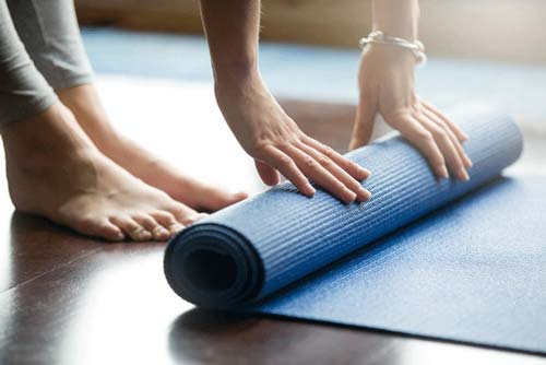 Close up of woman rolling out a blue yoga mat on the floor
