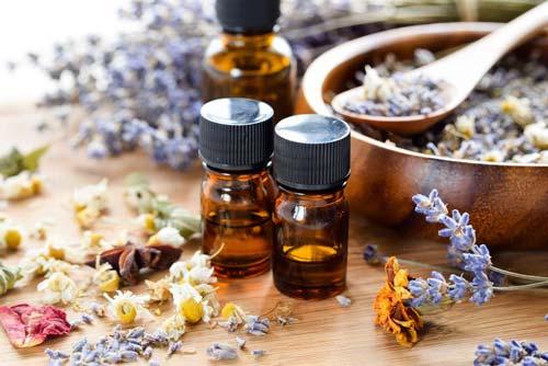 Three dark essential oil bottles with herbs around them