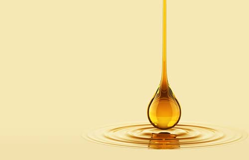 A drop of essential oil dropping into liquid