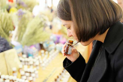Woman with brown hair sniffing an essential oil bottle.