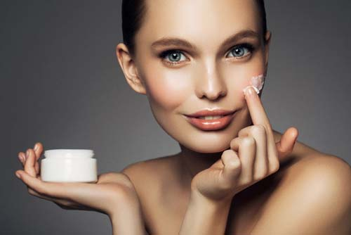 Beautiful woman putting skin cream on her face