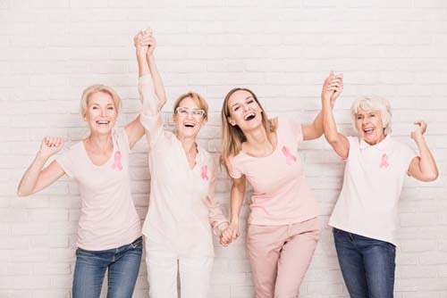 Group of ladies wearing breast cancer ribbons cheering