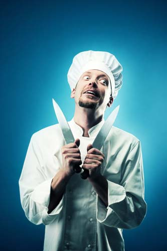 Chef with a crazy look on his face, holding a knife.