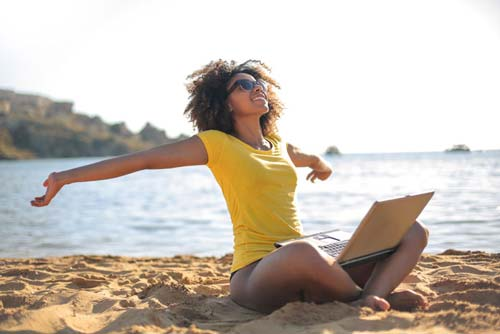 Girl relaxing at the beach with a laptop in her lap