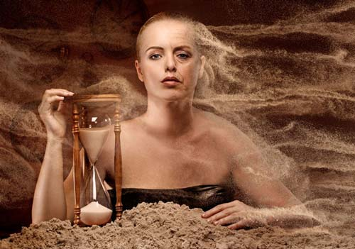 woman in sand up to her chest holding an hourglass, she' changing from young to old