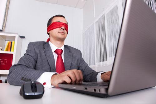 Blindfolded businessman working on laptop