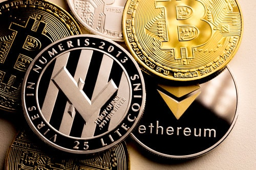 Close up shot of three main cryptocurrencies; bitcoin, ethereum and litecoin in dark surface.