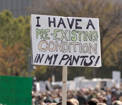 Pre existing condition sign at a rally