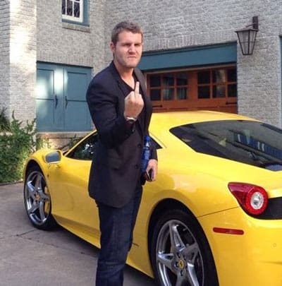 Alex Becker giving middle finger standing in front of yellow Ferrari